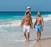 Three generations of men walking on the beach at Now Resorts & Spas
